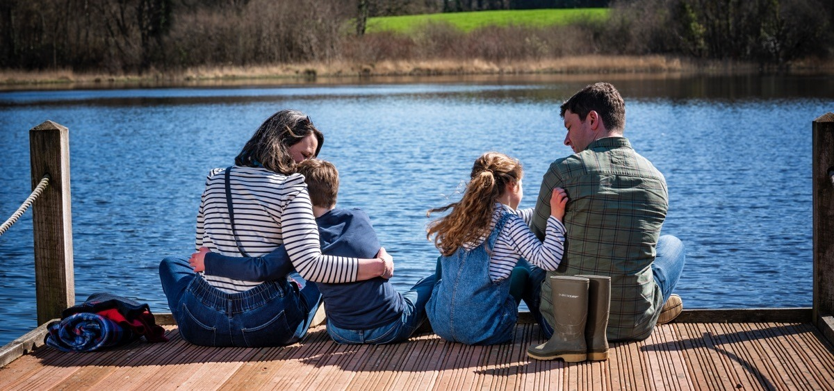 Family sitting on jetty at Blessingbourne Estate